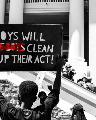 protestor in front of windhoek parliament holding sign saying boys will be boys but the part that says 'be boys' is scratched out and replaced with the words 'clean up their act!'.